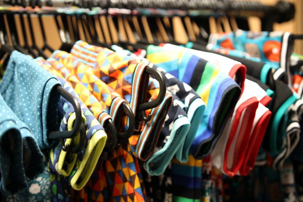 Pohled na řadu barevně zajímavých triček s krátkým rukávem na ramínkách.