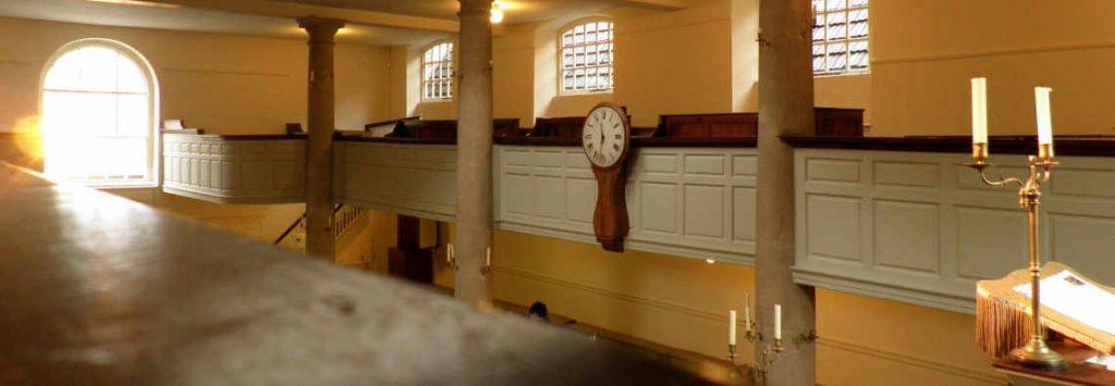 Pohled do modlitebny metodistického hnutí v Bristolu. Vpravo kazatelna s otevřenou Biblí a svícnem, ve středu na ostění galerie velké výrazné hodiny s časem 11.32 a vlevo proti kazatelně krásně prosluněné okno.